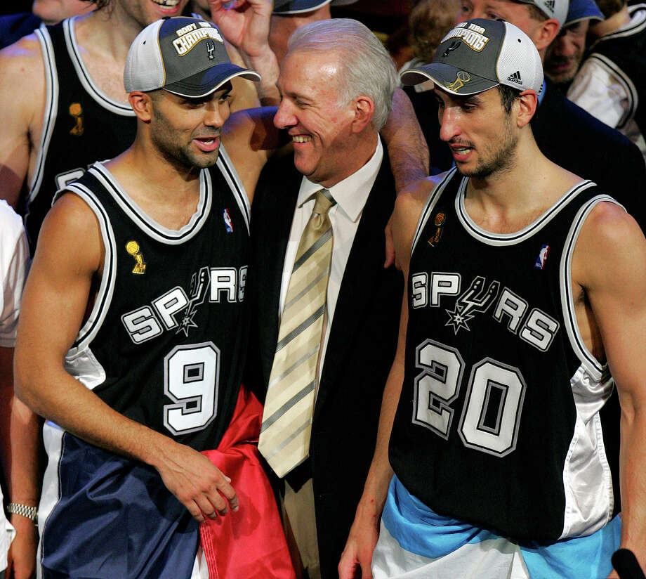 Spurs' guard Tony Parker (9), coach Gregg Popovich and guard Manu Ginobili (20) enjoy their NBA championship and postgame celebration in Cleveland on June 14, 2007. Photo: BAHRAM MARK SOBHANI, SAN ANTONIO EXPRESS-NEWS / SAN ANTONIO EXPRESS-NEWS