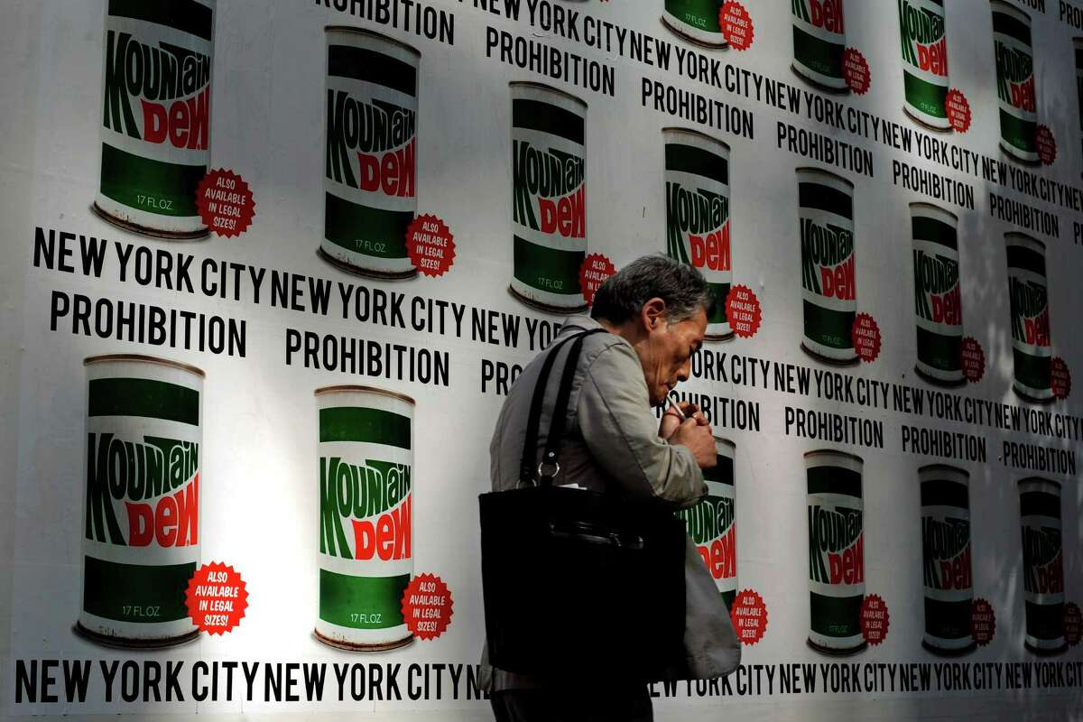 A man lights a cigarette as he walks past an advertisement created in collaboration with Mountain Dew and New York Art Department, Thursday, Sept. 13, 2012, on 13th Street in New York. New York City cracked down on supersized sodas and other sugary drinks Thursday in what is celebrated as a groundbreaking attempt to curb obesity and condemned as a breathtaking intrusion into people's lives by a mayor bent on creating a ?