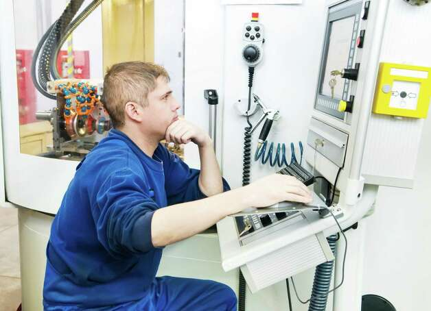 worker operating CNC machine center Photo: Dmitry Kalinovsky / iStockphoto
