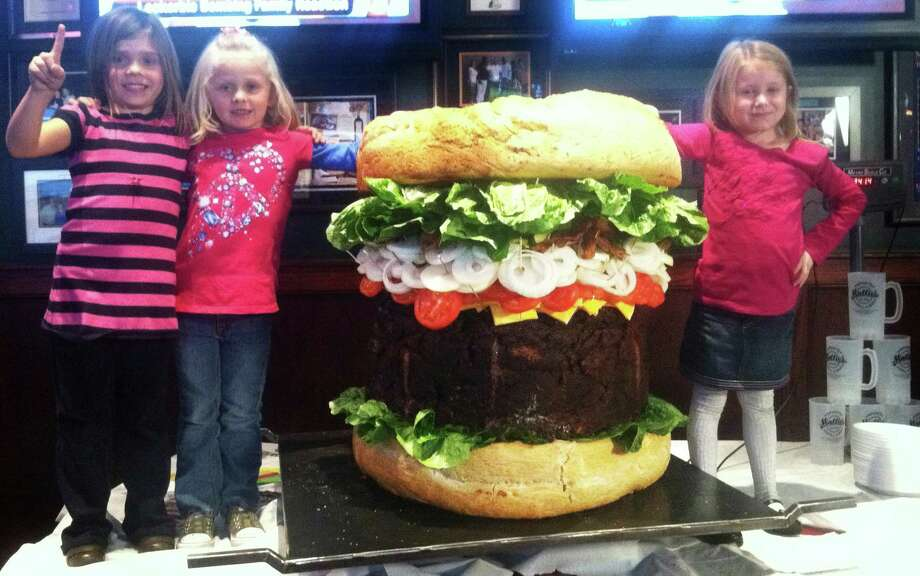 "Children stand next to a 338-pound ""Absulutely Ridiculous Burger"" at Mallie's Sports Grill in Southgate, Mich., on Oct. 20, 2011. The three foot-high sandwich packs 540,000 calories, takes 22 hours to cook and sells for $2,000. Manager Jason Jones says it comes with fries and a drink. Photo: AP Photo/Mallie's Sports Grill,  Mike Matkin / Mallies Sports Grill"