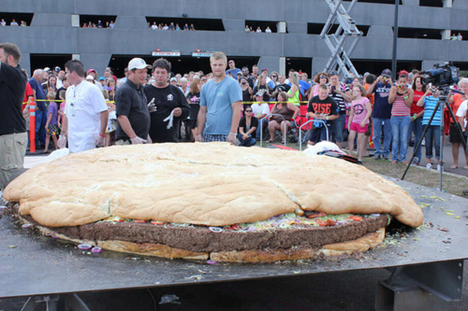 People examine a bacon cheeseburger measuring 10 feet in diameter and weighing more than a ton at Black Bear Casino Resort near Carlton, Minn., on Sept. 2, 2012. The behemoth burger tipped the scales at 2,014 pounds. Photo: AP Photo/Black Bear Casino Resort / Black Bear Casino Resort