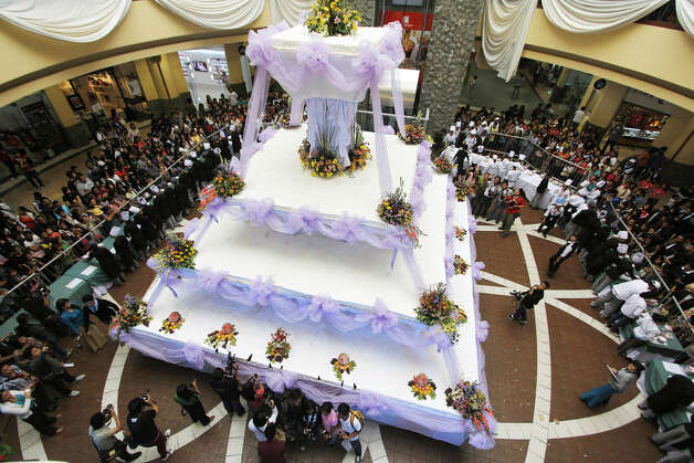 People gather at the unveiling of Baguio city's largest chocolate wedding cake during the opening of the Hotel and Restaurant Association's annual culinary competition Thursday, Sept. 6, 2012, in the northern Philippines. The four-layered cake, measuring 24x24 feet at its base, with a height of 40 feet and weighing more than 5 tons, is enough to serve around 15,000 people, according to organizers. Photo: Dave Leprozo Jr.,  Associated Press / AP