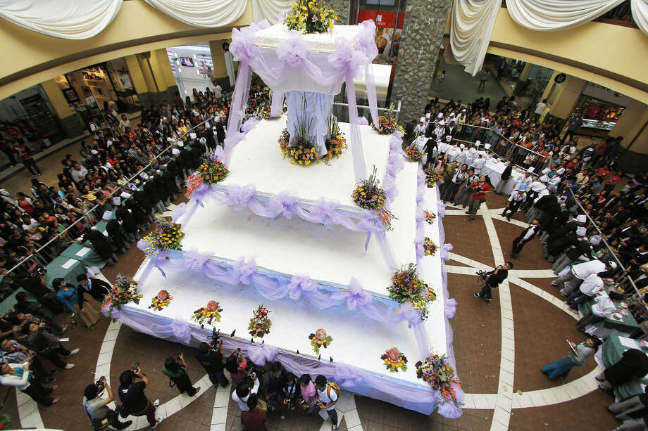 People gather at the unveiling of Baguio City's largest chocolate wedding cake during the opening of the Hotel and Restaurant Association's annual culinary competition on Sept. 6, 2012, in the northern Philippines. The four-layered cake, measuring 24 feet by 24 feet at its base, is 40 feet high and weighs more than 5 tons. It is enough to serve around 15,000 people, according to organizers. Photo: Dave Leprozo Jr.,  Associated Press / AP