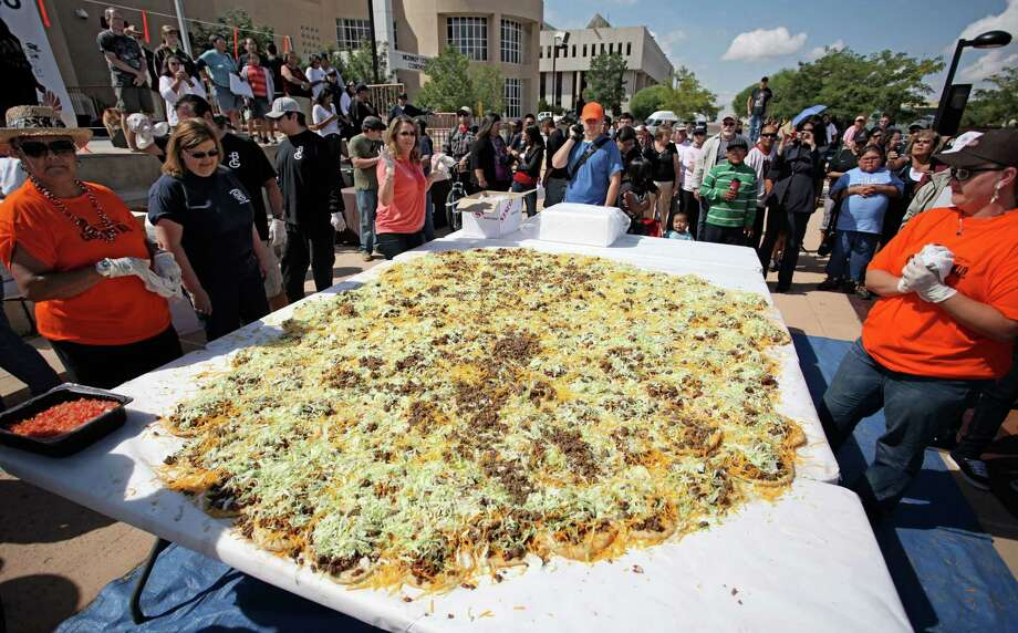 "Gallup, N.M., residents help build what state officials are calling the ""world's largest Navajo taco"" on Sept. 10, 2011. Organizers say no world record exists for the largest Navajo taco, so they built one using 150 pieces of fry bread and 30 pounds of green chile. According to volunteers and state officials, the Navajo taco was more than 10 feet in diameter and also needed 65 pounds of ground beef, 65 pounds of beans, 50 pounds of lettuce and 90 pounds of cheese. Photo: AP Photo/New Mexico Tourism Department / New Mexico Tourism Departmen"