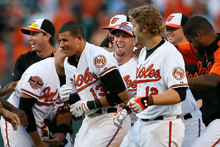 Manny Machado #13 of the Baltimore Orioles (C) is mobbed by teammates after driving in the winning run to give the Orioles a 3-2 win over the Tampa Bay Rays in fourteen innings at Oriole Park. Photo: Rob Carr, Getty Images