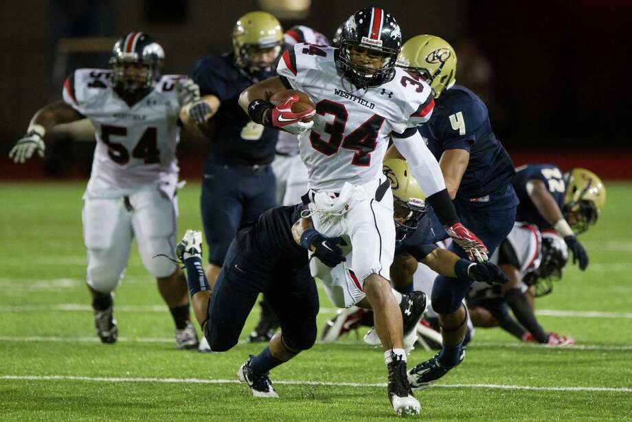Westfield running back Emmitt Raleigh (34) is tripped up by Klein Collins defensive back Jeremy Winchester (4) during the first half of a high school football game at at Klein Memorial Stadium on Thursday, Sept. 13, 2012, in Houston. Photo: Smiley N. Pool, Houston Chronicle / © 2012  Houston Chronicle