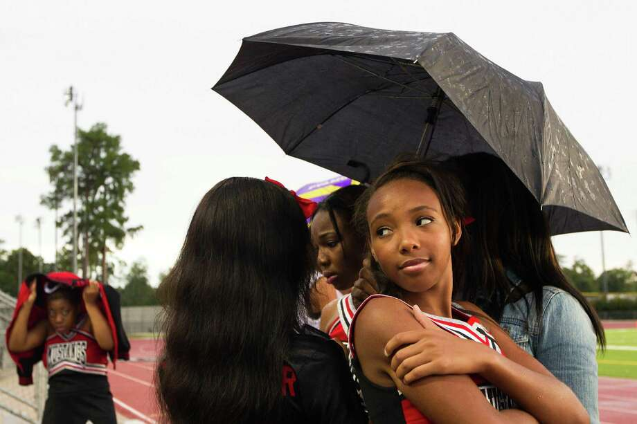 Westfield cheerleaders take cover against a light rain before a high school football game against Klein Collins at at Klein Memorial Stadium on Thursday, Sept. 13, 2012, in Houston. Photo: Smiley N. Pool, Houston Chronicle / © 2012  Houston Chronicle