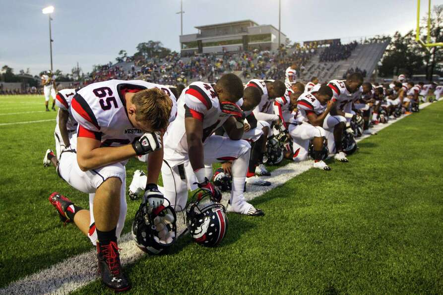 Westfield players, including Justin Johnson (65) and Tony Qualls (44) kneel in prayer before facing