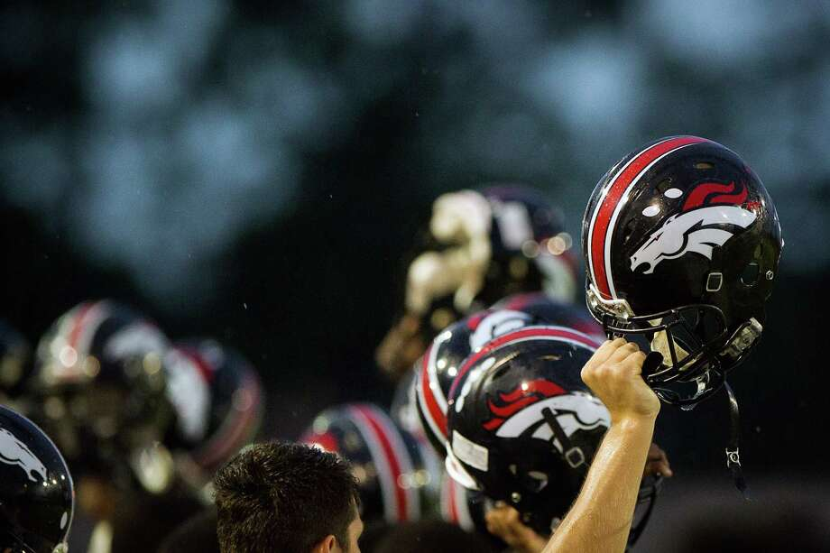 Westfield players lift their helmets before the kickoff of a high school football game against Klein Collins at at Klein Memorial Stadium on Thursday, Sept. 13, 2012, in Houston. Photo: Smiley N. Pool, Houston Chronicle / © 2012  Houston Chronicle