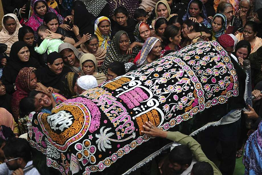 Mourners and relatives gather around a coffin during a funeral for a garment factory victim in Karachi on September 13, 2012. Pakistan on September 13 registered murder charges against factory bosses and government officials over the deaths of 289 people in the country's worst industrial disaster, police said. Photo: Asif Hassan, AFP/Getty Images