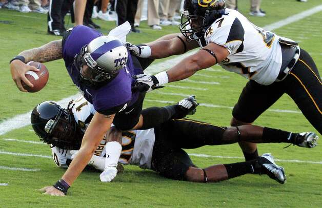 TCU quarterback Casey Pachall (4) dives against Grambling State defensive backs De'Vontay Hogan (10) and Tyler Smith (47) during the first half of an NCAA college football game in Fort Worth, Texas, Saturday, Sept. 8, 2012. (AP Photo/LM Otero) Photo: LM Otero, Associated Press / AP