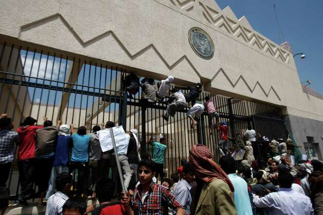 "Yemeni protesters climb the gate of the U.S. Embassy during a protest about a film ridiculing Islam's Prophet Muhammad, in Sanaa, Yemen, Thursday, Sept. 13, 2012. Dozens of protesters gather in front of the US Embassy in Sanaa to protest against the American film ""The Innocence of Muslims"" deemed blasphemous and Islamophobic. (AP Photo/Hani Mohammed) Photo: Hani Mohammed"