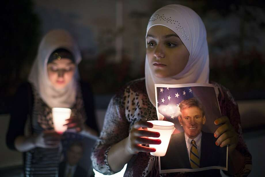 Dilan Samo, 13, holds a picture of slain U.S. ambassador to Libya Christopher Stevens during a candlelight vigil outside the Libyan Embassy, Thursday, Sept. 13, 2012, in New York. Stevens was killed by an angry mob during an assault on the American embassy in Benghazi that stemmed from the widespread anger generated by an American made anti-Muslim film. Photo: John Minchillo, Associated Press