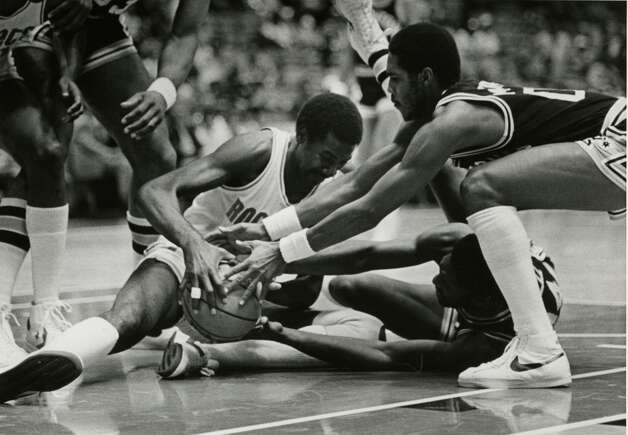 The Houston Rockets' Caldwell Jones (left) fights for the ball against the Spurs' Johnny Moore (top) and Bill Willoughby during the 1982-83 season. Photo: Houston Chronicle File Photo