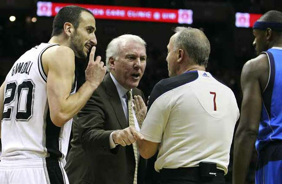 Spurs' coach Gregg Popovich (center) argues with official Kevin Fehr (07) after a questionable play by Dallas Mavericks' Jason Terry on Spurs' Manu Ginobili in the first half at the AT&T Center on Friday, Jan. 14, 2011.  Kin Man Hui/kmhui@express-news.net Photo: KIN MAN HUI, SAN ANTONIO EXPRESS-NEWS / San Antonio Express-News