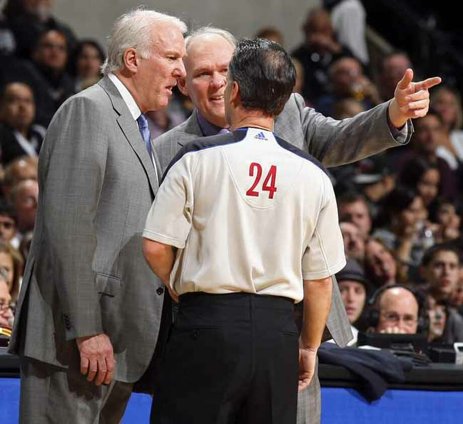 FOR SPORTS - Spurs head coach Gregg Popovich and Nuggets head coach George Karl talk with official Mike Callahan during first half action Sunday Jan. 16, 2011 at the AT&T Center. (PHOTO BY EDWARD A. ORNELAS/eaornelas@express-news.net) Photo: EDWARD A. ORNELAS, SAN ANTONIO EXPRESS-NEWS / eaornelas@express-news.net