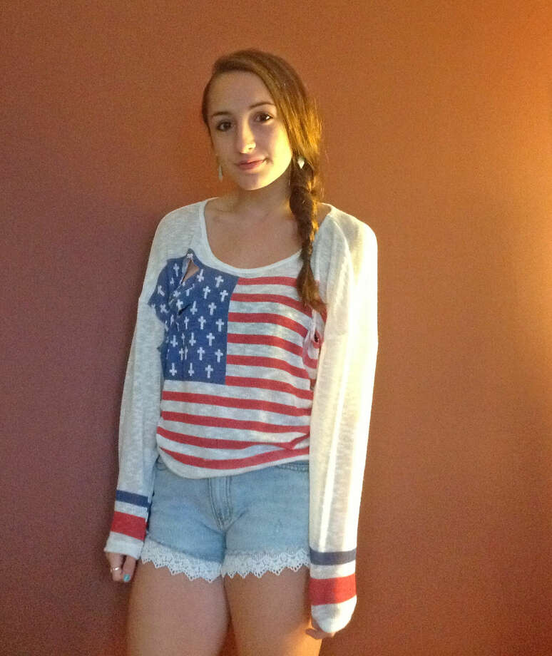 Kiersten Czuwala, from Hoosic Valley High School, Grade 9, trying on her new clothes for school wearing an American flag, baggy sweater and high-waisted jean shorts, with lace. Photo by Erik DeFruscio. Photo: New Visions: Journalism & Media Studies