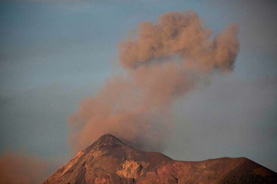 Volcan de Fuego or Volcano of Fire blows outs a thick cloud of ash as seen from Antigua Guatemala, F
