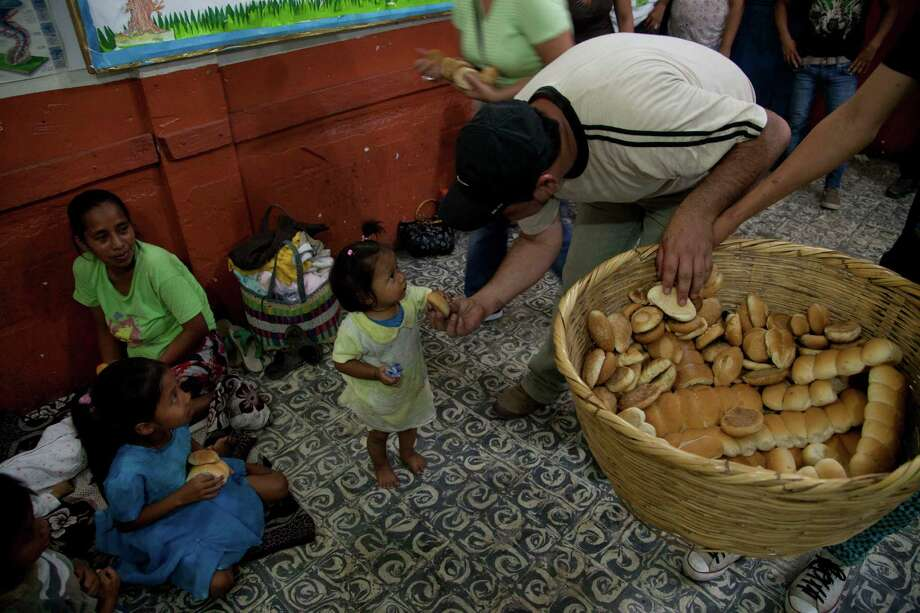 Volunteers distribute food to evacuated from communities near the Volcan de Fuego, or Volcano of Fire, at shelter in Santa Lucia Cotzumalguapa, south of Guatemala City, late Thursday. The long-simmering volcano exploded with a series of powerful eruptions outside one of Guatemala's most famous tourist attractions on Thursday, hurling thick clouds of ash and spewing rivers of lava down its flanks. (AP Photo/Moises Castillo) Photo: Ap/getty
