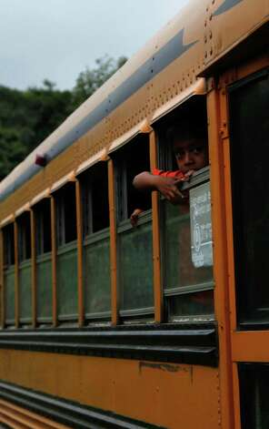 A boy peers from the window of a government provided bus during evacuations away from the Volcan del Fuego, or Volcano of Fire, to a shelter as they leave the village of Morelia, Guatemala, Thursday. The long-simmering volcano exploded with a series of powerful eruptions outside one of Guatemala's most famous tourist attractions on Thursday, hurling thick clouds of ash in the air and spewing rivers of lava down its flanks. (AP Photo/Moises Castillo) Photo: Ap/getty
