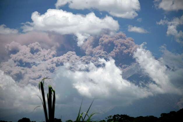 Volcanic ash spews from the Volcan de Fuego or Volcano of Fire as seen from Palin, south of Guatemala City, Thursday. The long-simmering volcano exploded into a series of powerful eruptions Thursday, hurling thick clouds of ash nearly two miles (three kilometers) high, spewing rivers of lava down its flanks and forcing the evacuation of more than 33,000 people from surrounding communities. (AP Photo/Moises Castillo) Photo: Ap/getty