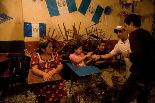 People evacuated from Morelia in Chimaltenango sit in a shelter in a public school of Santa Lucia Cotzumalguapa, Escuintla department, 90 km south of Guatemala City, on Thursday after their village was threatened by columns of ash released by the Volcan de Fuego.  Guatemala's Volcano of Fire had its strongest eruption in a decade, prompting the evacuation of around 33000 people, officials announced. The eruption created massive columns of smoke that could be seen from the capital, some 75 km away. (JOHAN ORDONEZ/AFP/GettyImages) Photo: JOHAN ORDONEZ, Ap/getty / 2012 AFP
