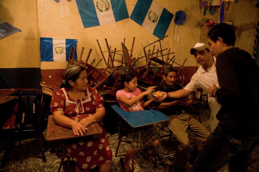 People evacuated from Morelia in Chimaltenango sit in a shelter in a public school of Santa Lucia Co