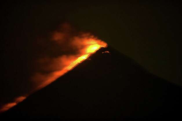 The Fuego volcano erupts, as seen from the Palin municipality,  south of Guatemala City on Thursday. The volcano has begun spewing lava and columns of ash into the air, and authorities have raised the alert level in the area. Guatemala's Volcano of Fire had its strongest eruption in a decade on Thursday, prompting the evacuation of around 33 thousand people, officials announced. The eruption created massive columns of smoke that could be seen from the capital, some 75 kilometers away. (JOHAN ORDONEZ/AFP/GettyImages) Photo: JOHAN ORDONEZ, Ap/getty / 2012 AFP
