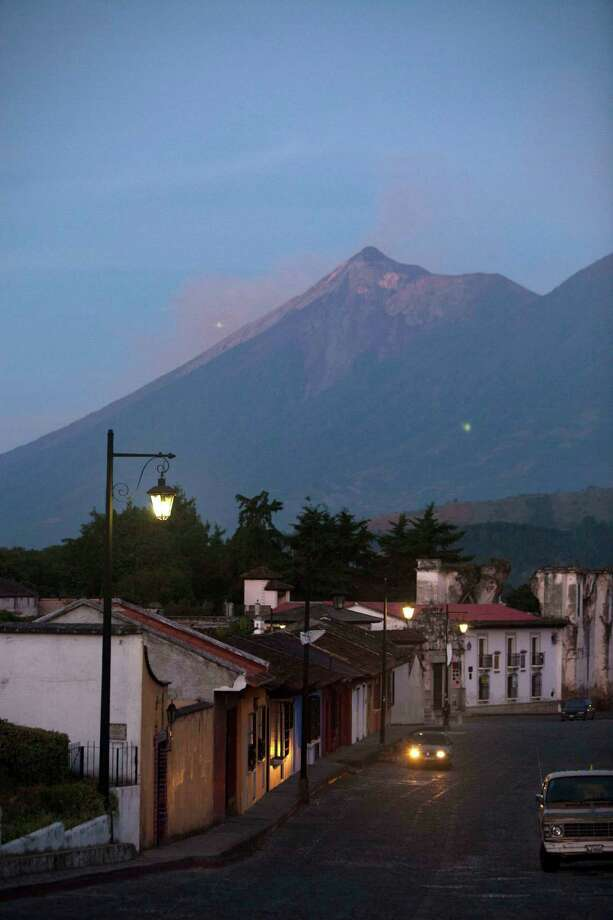 A car drives through the cobblestones streets of Antigua Guatemala, backdropped by the Volcan de Fuego or Volcano of Fire, Friday. The volcano spewed rivers of bright orange lava down its flanks on Thursday. Authorities ordered more than 33,000 people from nearby communities evacuated. (AP Photo/Moises Castillo) Photo: Ap/getty