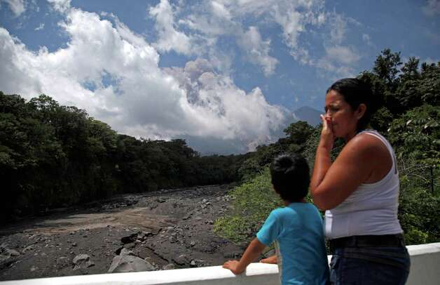 A boy watch plumes of smoke and volcanic ash rise from the Volcan de Fuego or Volcano of Fire, as seen from Palin, south of Guatemala City, Thursday. The long-simmering volcano exploded into a series of powerful eruptions Thursday, hurling thick clouds of ash nearly two miles (three kilometers) high, spewing rivers of lava down its flanks and forcing the evacuation of more than 33,000 people from surrounding communities. (AP Photo/Moises Castillo) Photo: Ap/getty