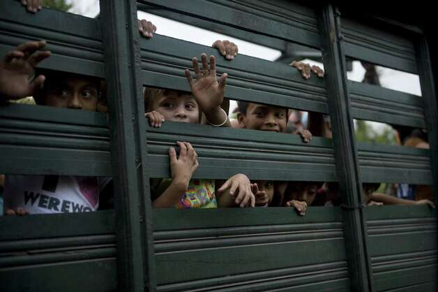 Children ride in the back of an army truck after being evacuated from Morazan in Chimaltenango department, 125 kilometers outh of Guatemala City on Thursday after the village was affected by columns of ash released by the Volcan de Fuego. Guatemala's Volcano of Fire had its strongest eruption in a decade on Thursday, prompting the evacuation of around 33 thousand people, officials announced. The eruption created massive columns of smoke that could be seen from the capital.  (JOHAN ORDONEZ/AFP/GettyImages) Photo: JOHAN ORDONEZ, Ap/getty / 2012 AFP