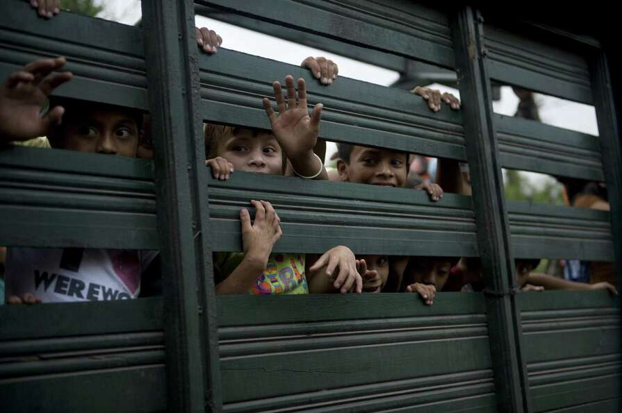 Children ride in the back of an army truck after being evacuated from Morazan in Chimaltenango depar