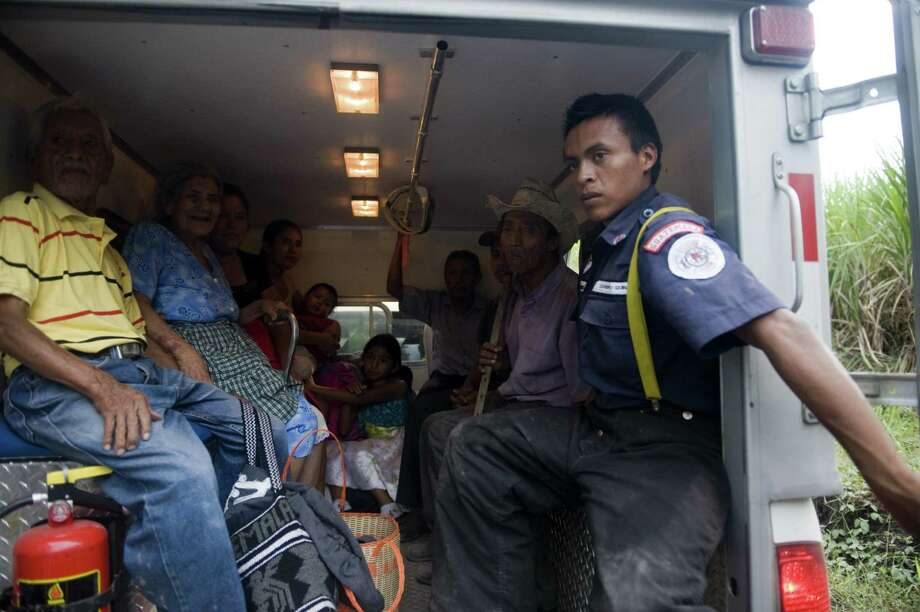 People after being evacuated from Morazan in Chimaltenango department, 125 kilometers south of Guatemala City on Thursday in an ambulance, after the village was affected by columns of ash released by the Volcan de Fuego. Guatemala's Volcano of Fire had its strongest eruption in a decade on Thursday, prompting the evacuation of around 33 thousand people, officials announced. The eruption created massive columns of smoke that could be seen from the capital, some 75 kilometers away. (JOHAN ORDONEZ/AFP/GettyImages) Photo: JOHAN ORDONEZ, Ap/getty / 2012 AFP
