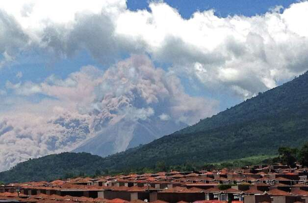 In this image with a cell phone plumes of smoke rise from the Volcan de Fuego or Volcano of Fire spews ash seen from Palin, south of Guatemala City, Thursday. The volcano is spewing lava and ash and the director of the national disaster agency says officials are carrying out a massive evacuation of thousands of people in five communities. (AP Photo/Moises Castillo) Photo: Ap/getty