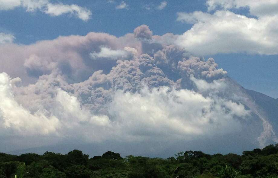 In this image with a cell phone, plumes of smoke rise from the Volcan de Fuego or Volcano of Fire as seen from Palin, south of Guatemala City, Thursday. The volcano is spewing lava and ash and the director of the national disaster agency says officials are carrying out a massive evacuation of thousands of people in five communities. (AP Photo/Moises Castillo) Photo: Ap/getty