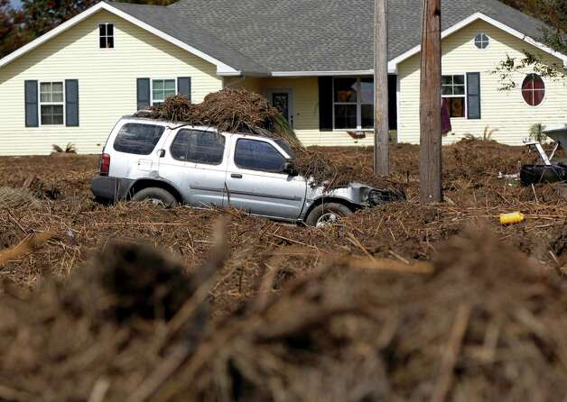 A car and lawn are covered in marsh grass after floodwaters from Hurricane Isaac receded in Braithwaite, La., Thursday, Sept. 6, 2012.  Isaac hit southeast Louisiana and coastal Mississippi last week, causing severe flooding and seven deaths. (AP Photo/Gerald Herbert) Photo: Gerald Herbert, STF / AP