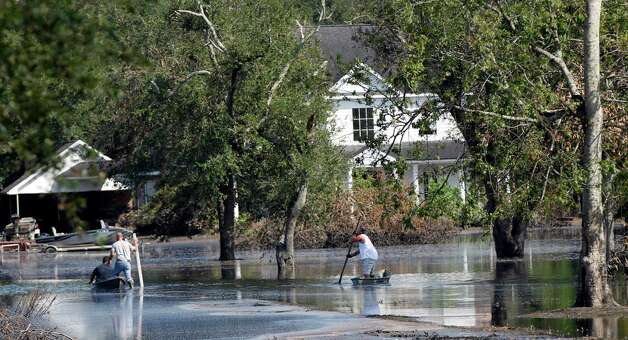 People use pirogues to get to a house as floodwaters from Hurricane Isaac recede in Braithwaite, La., Thursday, Sept. 6, 2012.  Isaac hit southeast Louisiana and coastal Mississippi last week, causing severe flooding and seven deaths. (AP Photo/Gerald Herbert) Photo: Gerald Herbert, STF / AP