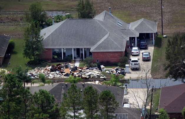 This aerial photo shows debris on a lawn as people gut their flooded homes in the aftermath of Hurricane Isaac in LaPlace, La., Wednesday, Sept. 5, 2012. (AP Photo/Gerald Herbert) Photo: Gerald Herbert, STF / AP