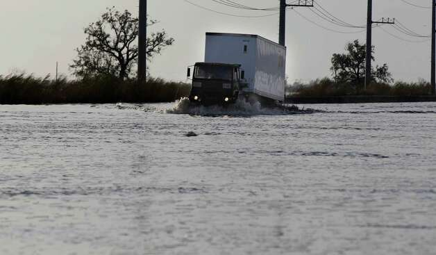 A truck drives through floodwaters from Hurricane Isaac on Hwy. 23, near Myrtle Grove, in Plaquemines Parish, La., Tuesday, Sept. 4, 2012. (AP Photo/Gerald Herbert) Photo: Gerald Herbert, STF / AP