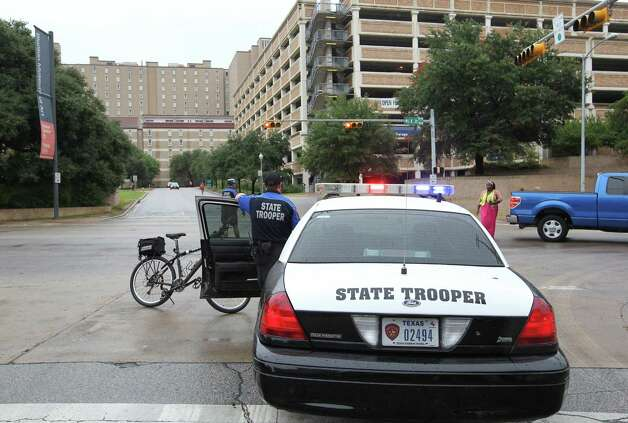 A police car blocks an intersection as buildings at the University of Texas campus in Austin, Texas, were evacuated after threates on Friday, September 14, 2012. Photo: Ralph Barrera/Austin American-Statesman/MCT / Austin American-Statesman