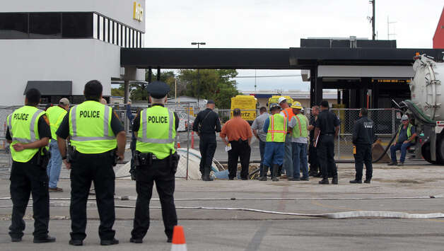 San Antonio firefighters and other workers monitor a fuel leak Friday September 14, 2012 on the west side of the San Antonio International Airport at a Hertz Rental Car area. San Antonio Fire Department Special Operations Chief Walter Yates said an underground 6,100 gallon tank at a refueling station for Hertz rental cars was being replaced when rain filled the pit it was in causing it to float and tip over. Yates said a layer of foam was places over the water and fuel mixture to mitigate vapors and that the liquid would be removed and disposed of. Photo: John Davenport / Express-News