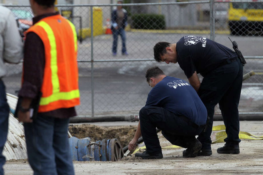 San Antonio firefighters (right) monitor a fuel leak Friday September 14, 2012 on the west side of the San Antonio International Airport at a Hertz Rental Car area. San Antonio Fire Department Special Operations Chief Walter Yates said an underground 6,100 gallon tank at a refueling station for Hertz rental cars was being replaced when rain filled the pit it was in causing it to float and tip over. Yates said a layer of foam was places over the water and fuel mixture to mitigate vapors and that the liquid would be removed and disposed of. Photo: John Davenport / Express-News