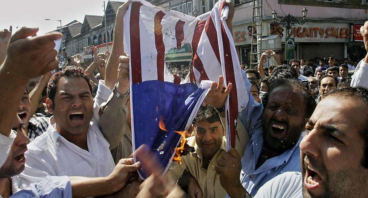 Kashmiri Muslims burn a mock American flag during a protest against an anti-Islam film called