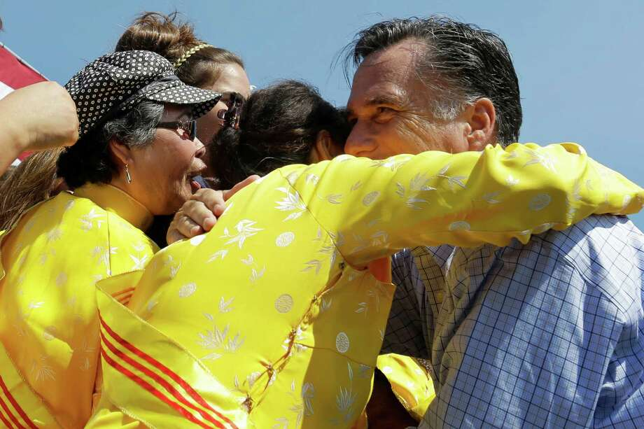 "Republican presidential candidate, former Massachusetts Gov. Mitt Romney embraces women wearing traditional Vietnamese ""ao dai"" dresses as he campaigns at Van Dyck Park in Fairfax, Va., Thursday, Sept. 13, 2012. (AP Photo/Charles Dharapak) Photo: Charles Dharapak, Associated Press / AP"