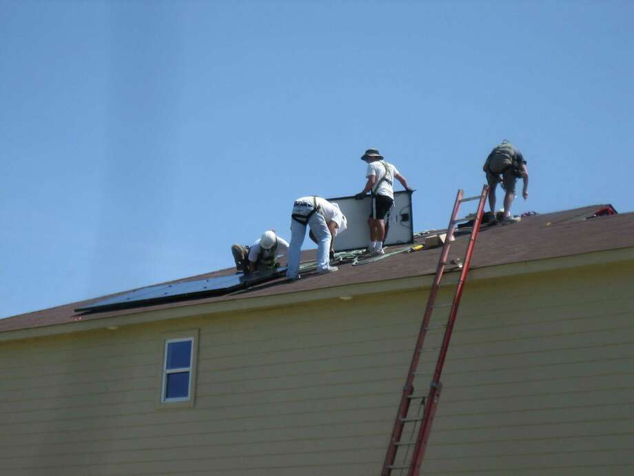 Workers from SunPower Corp. install solar panels on a home in the new Villa del Sol subdivision. Photo: Courtesy Photo