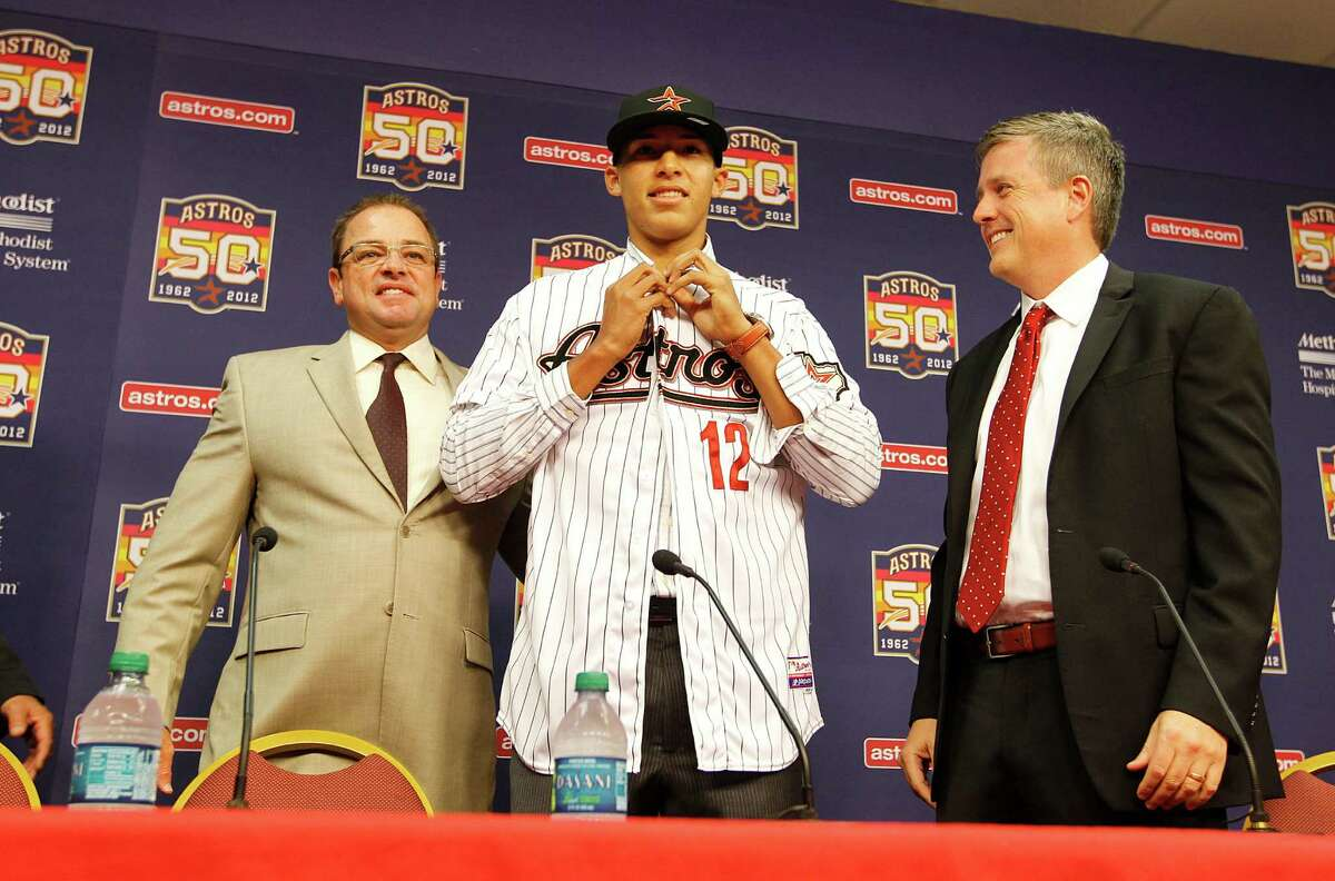 Carlos Correa, center, the Astros' No. 1 draft pick, signed with the team on June 7, 2012, in Houston.