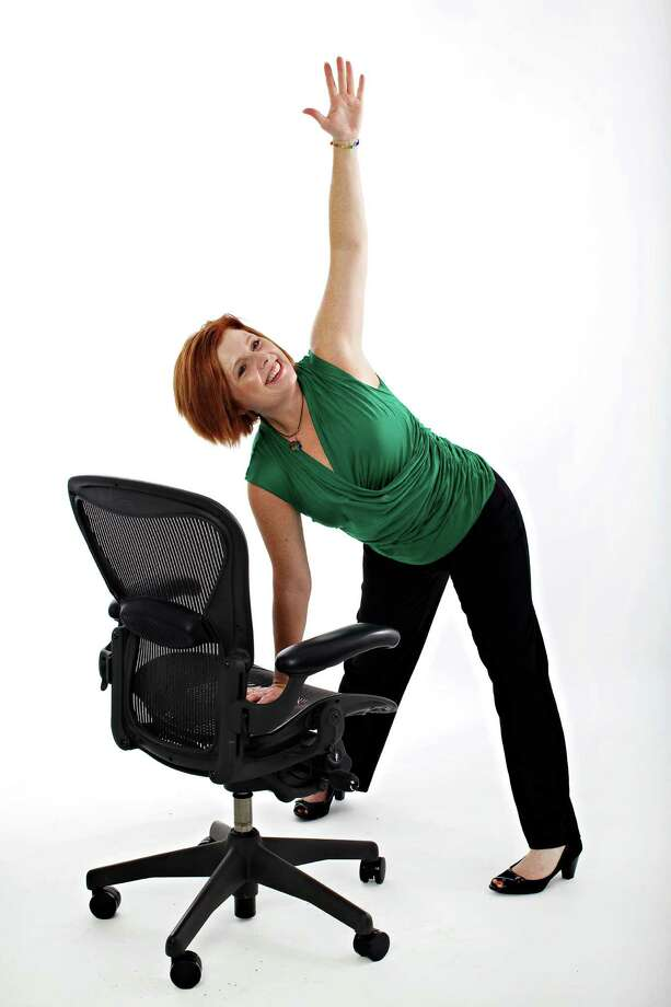 "Centeredbeing co-creator Suzie Carmack shows a ""pinwheel"" pose modified for the office. Photo: Deb Lindsey / WASHINGTON POST"
