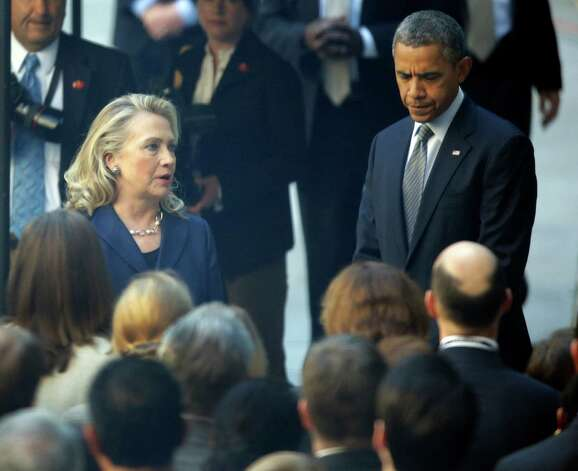 President Barack Obama, right, stands as Secretary of State Hillary Rodham Clinton, speaks to State Department personnel with concerning the recents deaths of Americans in Libya, in the courtyard of the State Department Wednesday, Sept. 12, 2012, in Washington. (AP Photo/Alex Brandon) Photo: Alex Brandon, Associated Press / AP
