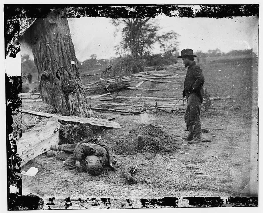 A Confederate soldier's body is tossed on the ground near the grave of a Union soldier at Antietam, Md., in 1862. Photo: Library Of Congress, PBS
