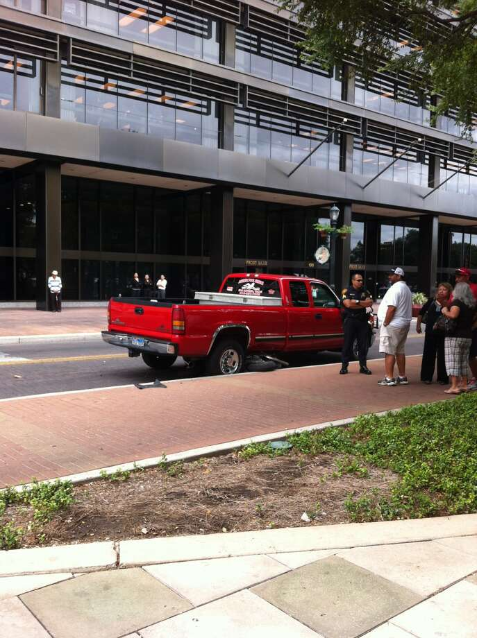 Police investigate the scene of a wreck on Houston and Main where a 21-year-old woman in a scooter was struck by a Chevrolet Silverado about 2 p.m. on Friday, September 14, 2012. Photo: Ana Ley / Express-News